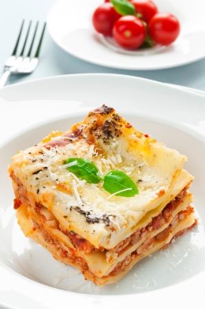 Portie lasagne met vlees bedekt met parmezaanse kaas Stockfoto
