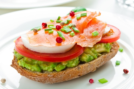 Sandwich with smoked salmon, avocado, tomato and egg