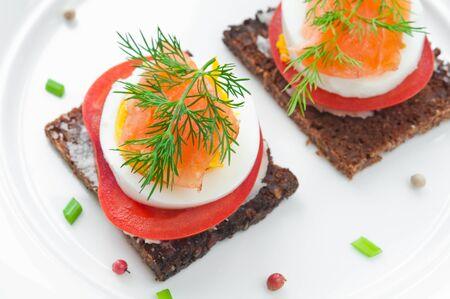 salmon ahumado: Sandwich con salmón ahumado, tomate y huevo cubierto con eneldo fresco