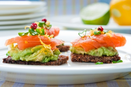 Brown bread sandwich with smoked salmon, avocado topped with chive and pepper photo