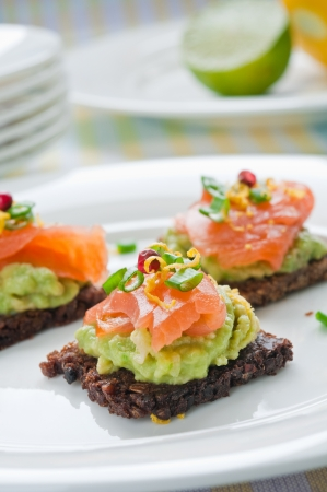 Brown bread sandwich with smoked salmon, avocado topped with chive and pepper Stock Photo