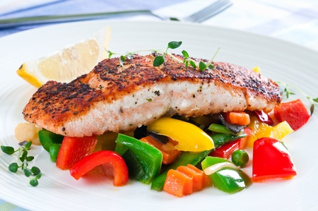 Grilled salmon with vegetables, herbs and lemon Stock Photo