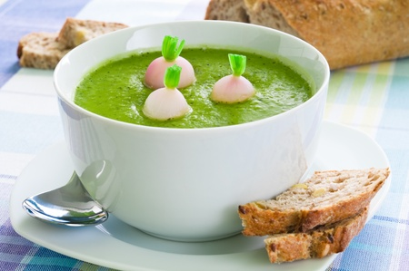 Fresh green peas soup with radish arranged with brown bread photo