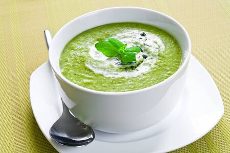 Fresh vegetable soup topped with cream and mint