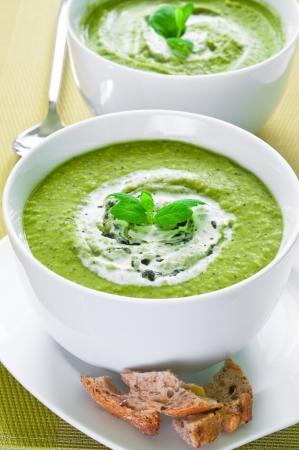 新鮮な野菜スープのクリームとミントをトッピング 写真素材