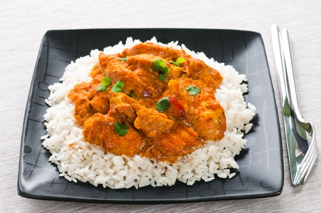 curry chicken: Chicken curry with rice on black plate with knife and fork Stock Photo
