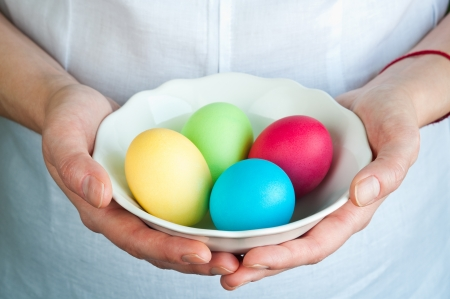 Hands holding bowl with colorful eggs photo