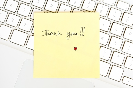Postit note saying Thank You arranged on a laptop keyboard