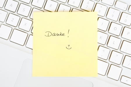 Postit note saying Danke arranged on a laptop keyboard photo
