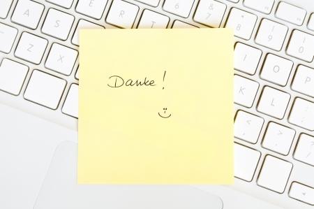 postits: Postit note saying Danke arranged on a laptop keyboard