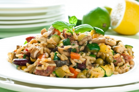 Risotto with chicken and vegetables on white plate photo