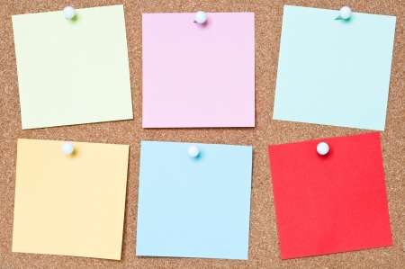 yellow tacks: Selection of blank adhesive notes attached to a cork board Stock Photo