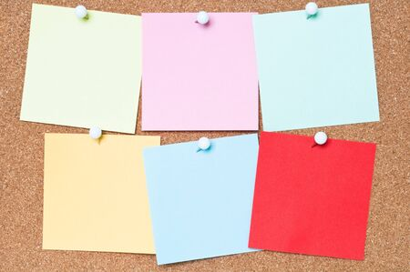 corkboard: Selection of blank adhesive notes attached to a cork board Stock Photo
