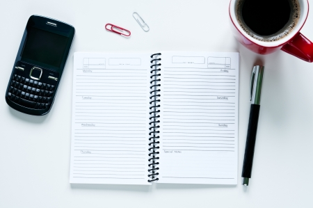 Blank notepad with mobile phone and cup of coffee arranged on white desk Stock Photo - 18656330