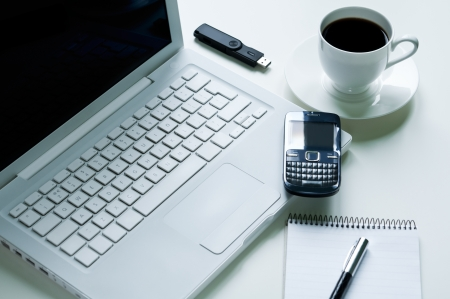Modern laptop with mobile phone, cup of coffee, notepad, fountain pen and usb pendrive photo