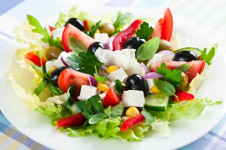 Closeup of fresh salad with feta cheese, tomato, cucumber, olives and lettuce