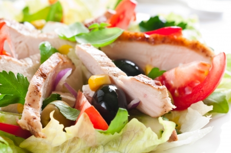 Close-up van kip salade met tomaat, sla en olijven