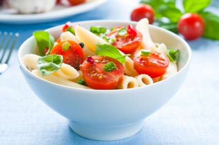 black dish: Pasta salad with penne, cherry tomatoes and basil