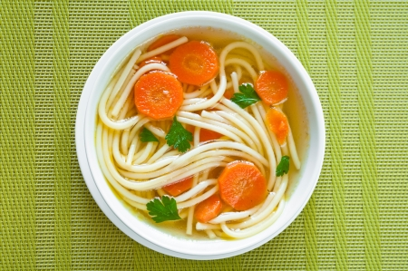 chicken soup: Chicken soup in a bowl with carrot and fresh parsley