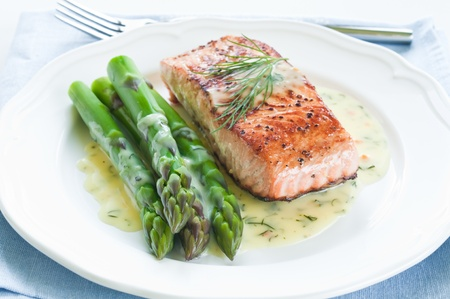 Grilled salmon with asparagus and dill sauce on white plate