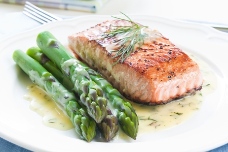 salmon dinner: Grilled salmon with asparagus and dill sauce on white plate