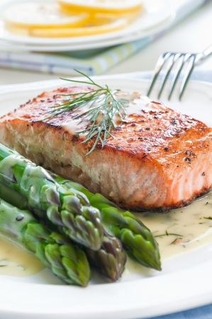 cooked fish: Grilled salmon with asparagus and dill sauce on white plate
