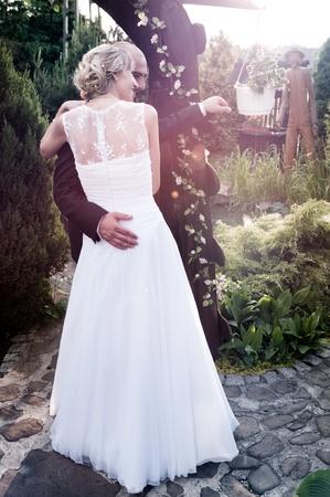 Bruid en bruidegom het stellen in de tuin in de middagzon Stockfoto