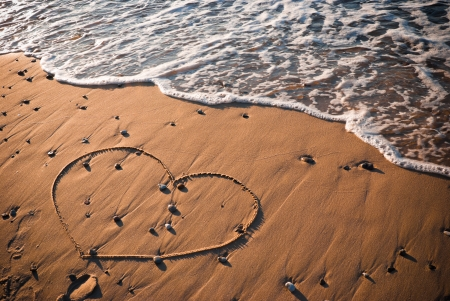 Heart shape written on sand with water in background  photo
