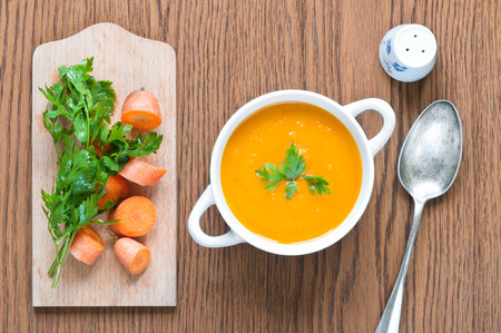Carrot soup close up with fresh carrot, parsley, spoon and salt shaker