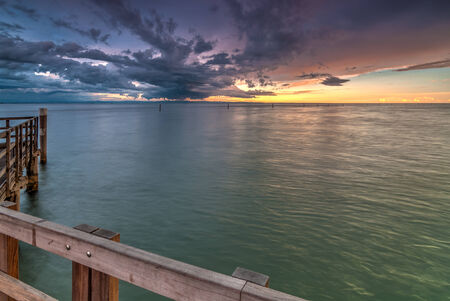 shore line: View from wooden pier over the sea with dramatic sky in the background Stock Photo