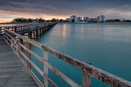 Kijken naar Lignano Sabbiadoro van houten pier bij zonsondergang Stockfoto - 32644633