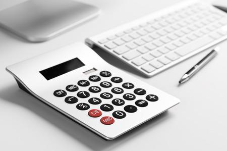 Een bureau met computer toetsenbord, rekenmachine en balpen Stockfoto