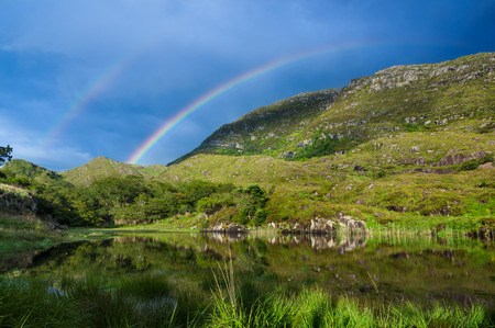 Colorful rainbow over green hills in Ireland Stock Photo