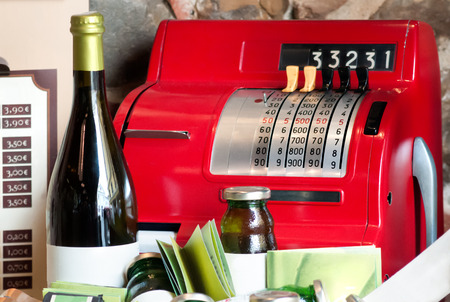wine register: An old vintage cash box arranged with a bottle of wine
