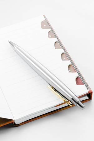 open diary: Open notepad with ballpoint on white background with plenty of copyspace