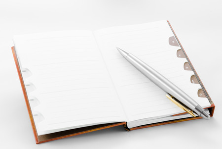 Open notepad with ballpoint on white background with plenty of copyspace photo