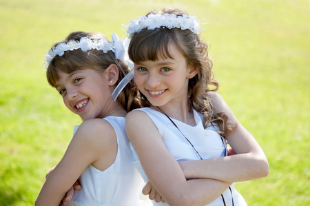 sister: Young girls doing her catholic first holy communion Stock Photo