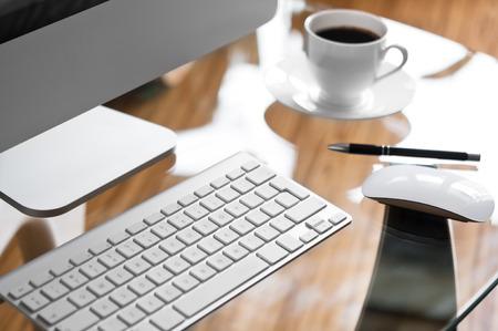 Glas bureau met moderne computer en een kopje koffie