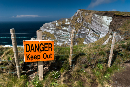 steep cliff sign: Warning sign on the edge of high cliffs in County Kerry, Republic of Ireland Stock Photo