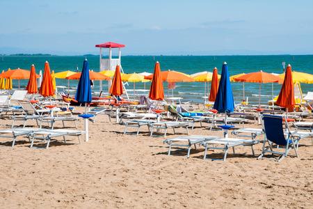 Zandstrand met kleurrijke parasols, stoelen en lifegard toren