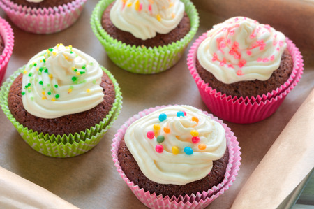 Fancy chocolate cupcakes with vanilla cream and colorful toppings and decoration photo