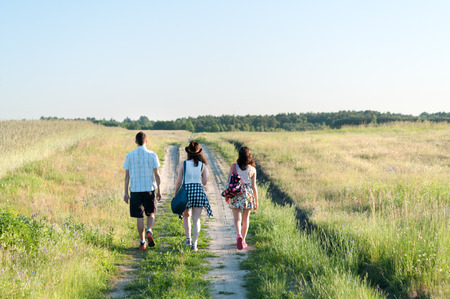 Young people walking away along country path