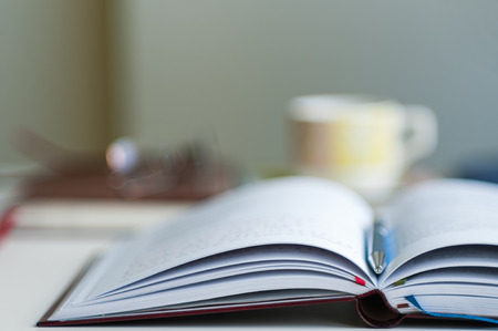 paper and pen: Close up of open notebook blurred with very shallow depth of field
