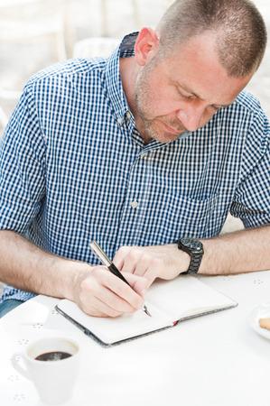 papel de notas: El hombre sentado a la mesa con la taza de caf� y la escritura en el bloc de notas