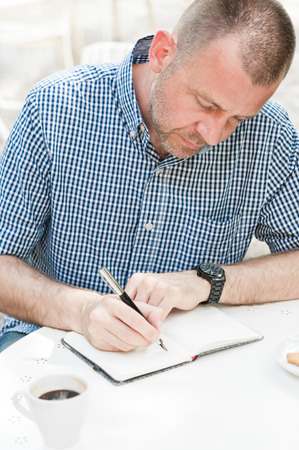 male hand: Man sitting at table with cup of coffee and writing in notepad