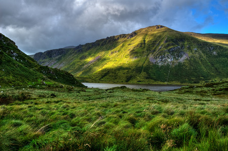 Sunny mountain and lake landscape on Dingle peninsula, Ireland