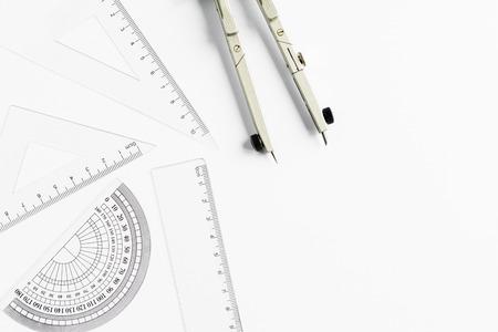 utiles escolares: Compás y demás equipo de medición sobre papel blanco