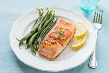 Grilled salmon fillet with green beans and lemon on white plate Stockfoto