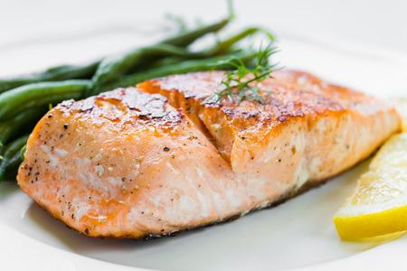 peces: Primer plano de filete de salmón a la plancha con judías verdes y limón en un plato blanco