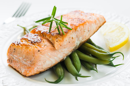 Close up of grilled salmon fillet with green beans and lemon on white plate Imagens
